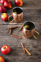High angle view of apples and cinnamons with drinks on wooden table