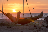 Side view of man reading book while lying in hammock at beach during sunset