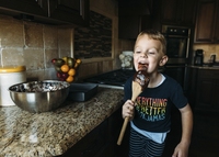 Happy boy licking spoon while standing in kitchen