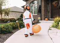 Rear view of boy in Halloween costume with container walking in yard