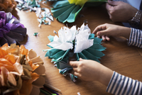 Cropped image of girl and father making paper flowers at table 11100054858| 写真素材・ストックフォト・画像・イラスト素材|アマナイメージズ