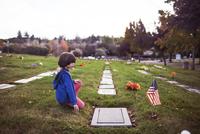 Side view of boy kneeling at cemetery 11100054936| 写真素材・ストックフォト・画像・イラスト素材|アマナイメージズ