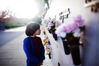 Boy looking at memorial wall while standing at sidewalk