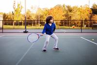 Boy playing tennis at court 11100054939| 写真素材・ストックフォト・画像・イラスト素材|アマナイメージズ