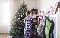 Smiling girl with Christmas socks at home 11100054945| 写真素材・ストックフォト・画像・イラスト素材|アマナイメージズ