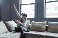 Businesswoman wearing virtual reality simulator gesturing in office 11100055059  写真素材・ストックフォト・画像・イラスト素材 アマナイメージズ
