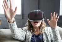 Businesswoman wearing virtual reality simulator in office 11100055060| 写真素材・ストックフォト・画像・イラスト素材|アマナイメージズ