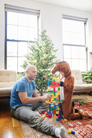 Father playing toy blocks with son dressed in costume at home 11100055186| 写真素材・ストックフォト・画像・イラスト素材|アマナイメージズ
