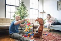 Father playing with son while girl sitting with pregnant woman at home 11100055187| 写真素材・ストックフォト・画像・イラスト素材|アマナイメージズ