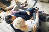 High angle view of senior couple video conferencing while sitting on sofa at home 11100055193| 写真素材・ストックフォト・画像・イラスト素材|アマナイメージズ