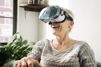 Happy senior woman wearing virtual reality simulator against wall at home 11100055212| 写真素材・ストックフォト・画像・イラスト素材|アマナイメージズ
