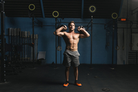 Shirtless man exercising with kettlebell in gym