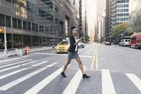 Woman holding smart phone while walking on crosswalk in city 11100055299| 写真素材・ストックフォト・画像・イラスト素材|アマナイメージズ