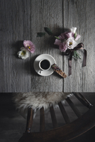 Overhead view of coffee and protein bar with flowers on wooden table