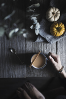Cropped image of woman with coffee by pumpkins at table
