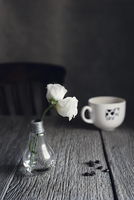 Roses in vase by coffee beans and cup on wooden table