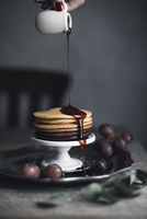 Cropped image of woman pouring syrup on pancakes at home