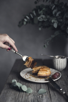 Cropped image of woman having pancakes at table