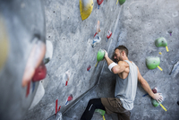 Determined athlete climbing on rock wall at gym
