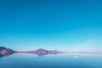 Distant view of woman standing at Bonneville Salt Flats against blue sky