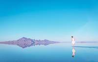 Woman walking in lake by mountain at Bonneville Salt Flats against blue sky 11100055689| 写真素材・ストックフォト・画像・イラスト素材|アマナイメージズ