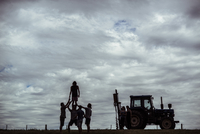 Friends enjoying while standing by tractor on field against cloudy sky