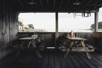 Picnic tables in old restaurant against beach