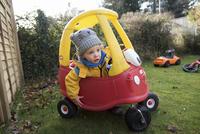 Girl driving toy car in backyard 11100055811| 写真素材・ストックフォト・画像・イラスト素材|アマナイメージズ