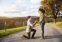 Man proposing surprised girlfriend on footpath