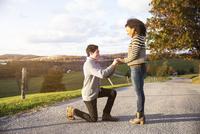Man proposing happy girlfriend on footpath