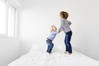 Happy siblings jumping on bed against wall at home 11100055920| 写真素材・ストックフォト・画像・イラスト素材|アマナイメージズ