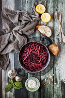 High angle view of healthy pink spaghetti on wooden table