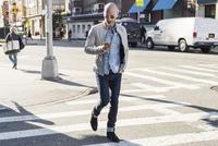 Man using mobile phone while walking on city street 11100056236| 写真素材・ストックフォト・画像・イラスト素材|アマナイメージズ