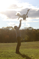 Side view of father playing with daughter while standing on grassy field 11100056915  写真素材・ストックフォト・画像・イラスト素材 アマナイメージズ
