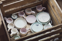 High angle view of various ceramics in wooden box at workshop