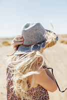 Woman in sun hat standing against at desert against clear sky during sunny day 11100057117| 写真素材・ストックフォト・画像・イラスト素材|アマナイメージズ