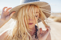 Close-up of woman in sun hat enjoying vacation at desert on sunny day