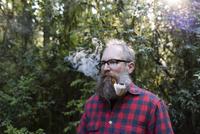 Man smoking pipe while standing against trees 11100057202| 写真素材・ストックフォト・画像・イラスト素材|アマナイメージズ