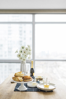 Food and drinks with flower vase arranged on dining table by window at home 11100057416| 写真素材・ストックフォト・画像・イラスト素材|アマナイメージズ