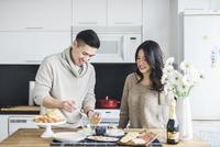 Woman looking at boyfriend preparing breakfast in kitchen 11100057428| 写真素材・ストックフォト・画像・イラスト素材|アマナイメージズ