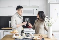 Happy couple toasting Prosecco in kitchen at home 11100057438| 写真素材・ストックフォト・画像・イラスト素材|アマナイメージズ