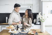 Happy couple with drinks looking at each other while standing in kitchen at home