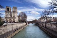 Notre Dame de Paris by river against cloudy sky