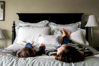 Mother and daughter lying on bed at home 11100057697| 写真素材・ストックフォト・画像・イラスト素材|アマナイメージズ