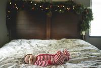 Cute baby girl lying on bed at home 11100057717| 写真素材・ストックフォト・画像・イラスト素材|アマナイメージズ