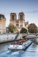 People traveling in boat on Seine River by Notre Dame de Paris against sky