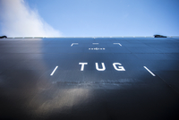 Low angle view of tug text on ship against sky