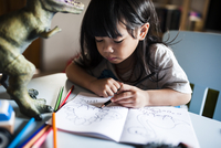 Girl drawing with colored pencils at home