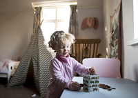 Girl putting coins in piggy bank while standing by table at home 11100058168| 写真素材・ストックフォト・画像・イラスト素材|アマナイメージズ