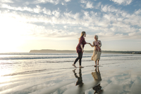 Playful family enjoying at beach against cloudy sky 11100058273| 写真素材・ストックフォト・画像・イラスト素材|アマナイメージズ